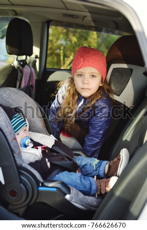 baby boy and little girl are sitting in the car chairs