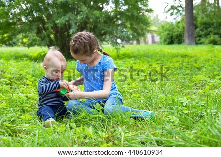 baby boy and little girl playing toy car on grass in park