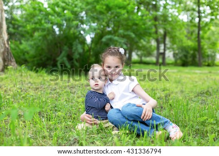 baby boy and little girl sitting on grass in park