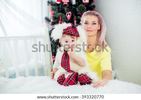 Baby boy and mother near Christmas tree - stock photo