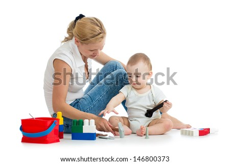 baby boy and mother play together with construction set toy