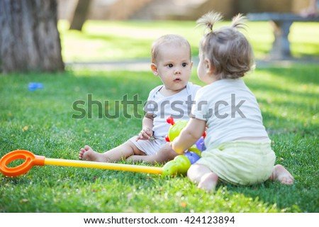 Baby boy and toddler girl playing while sitting on green grass in park - stock photo