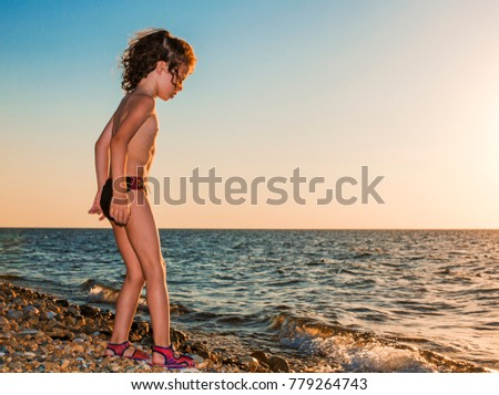 Baby boy barefoot are walking on the beach in water. Child on vacation in summer at the sea at sunset.