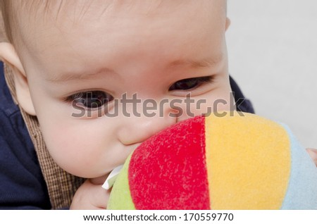 Baby boy biting a toy on a bed at home - stock photo