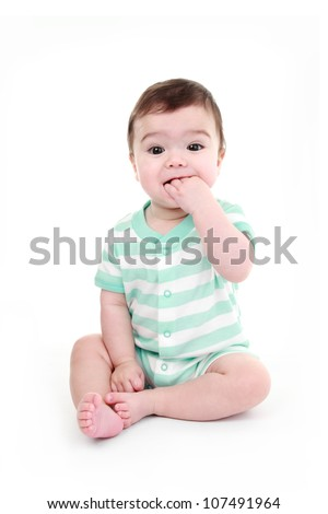 Baby boy biting his hand - stock photo