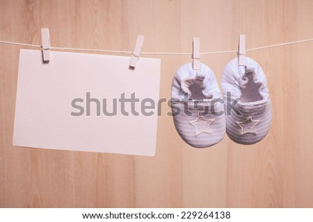 Baby boy booties attached to the rope and blank card for greetings - stock photo