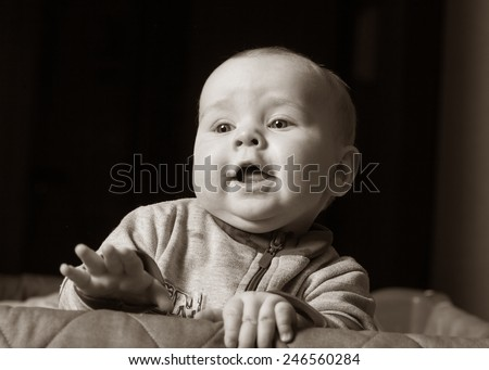 baby boy clinging to the crib - stock photo