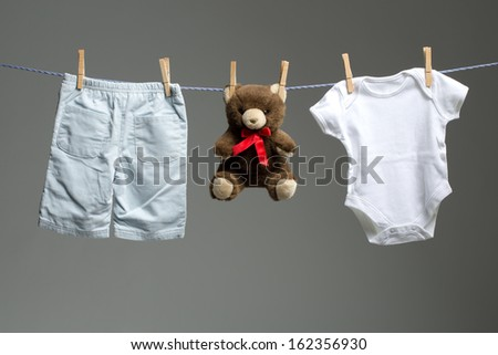 Baby boy clothes, a teddy bear on the clothesline - stock photo