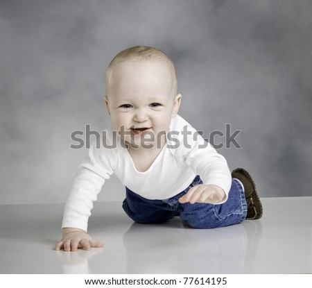 baby boy crawling toward camera, cute smile, t shirt and jeans, almost 1 yr old, two teeth visible