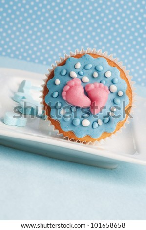 baby boy cupcake with feet and dots - stock photo