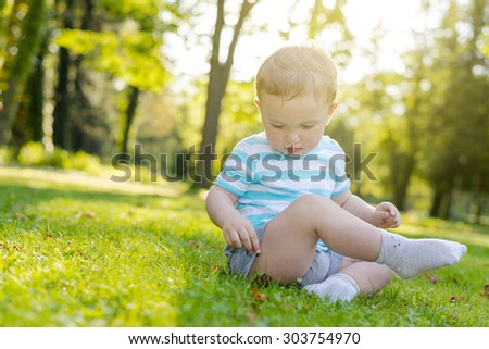 Baby boy discovering things in a city park - stock photo