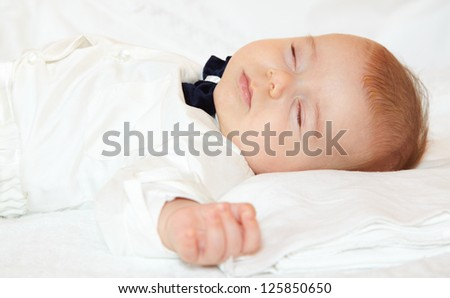 Baby boy dressed for party sleeping peacefully. - stock photo