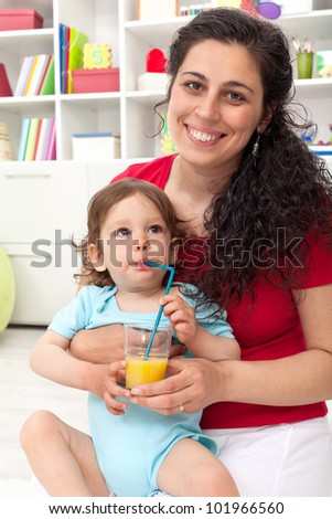 Baby boy drinking fruit juice - mother helping him - stock photo