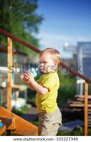 Baby boy drinking juice outdoors - stock photo
