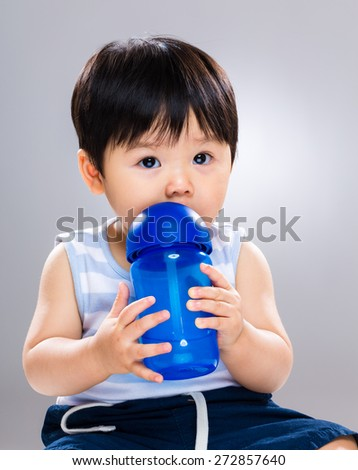 Baby boy drinking water - stock photo