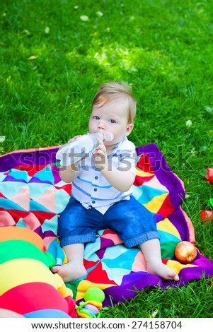 Baby boy drinking water in park, holding bottle - stock photo