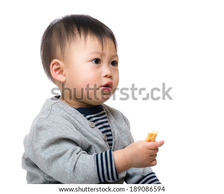 Baby boy eating biscuit