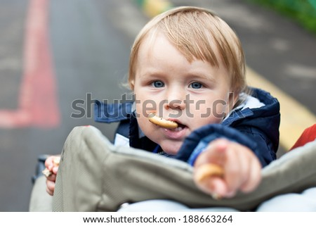 Baby boy eating cakes in stroller - stock photo