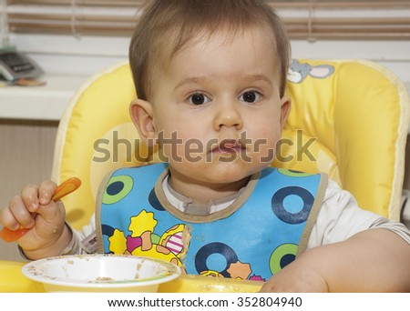 Baby boy eating in high chair, messy face, one year old - stock photo