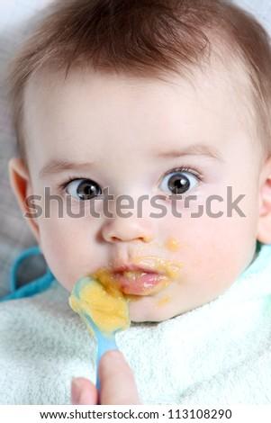 Baby boy eating vegetable mash - stock photo