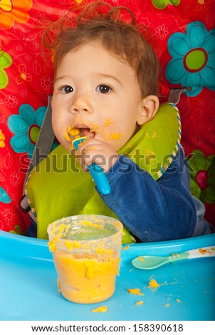 Baby boy eating vegetables puree by yourself and sitting in chair - stock photo