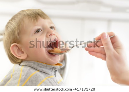 Baby boy fed by his mom at home - stock photo