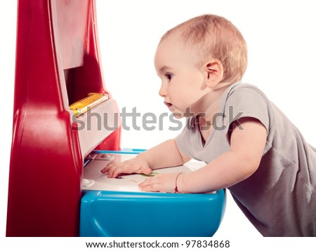 Baby boy hanging onto baby work desk. 9 month old boy trying to stay on his feet holding onto a baby work bench. - stock photo