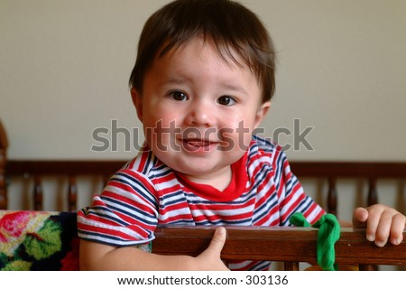 Baby boy in a crib hanging onto the side - stock photo