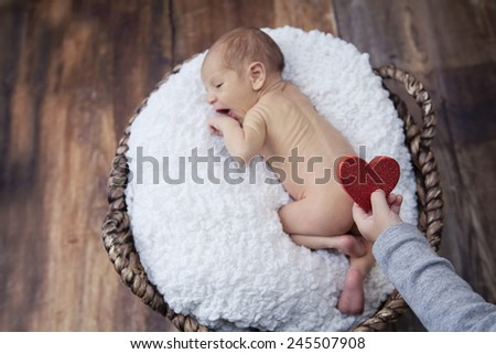 Baby boy in a wooden basket for Valentines day - stock photo