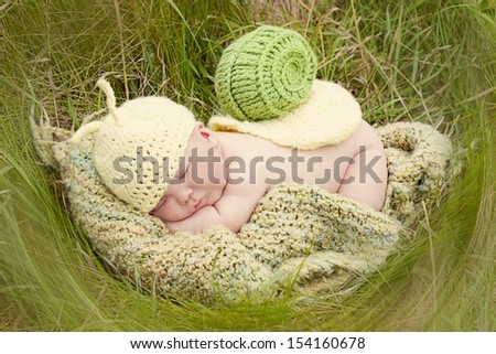 Baby boy in an outdoor portrait setting dressed up as a snail. - stock photo