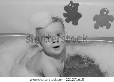 Baby boy in bath sepia filter - stock photo