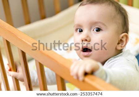 Baby boy in his bed - stock photo