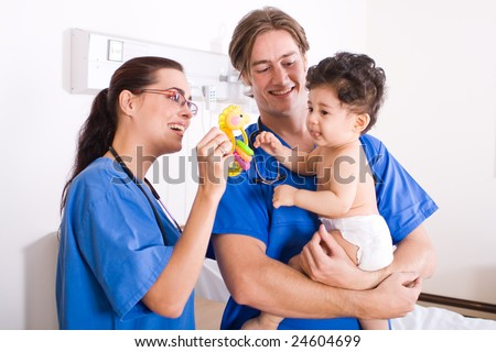 baby boy in hospital ward with doctor and nurse - stock photo