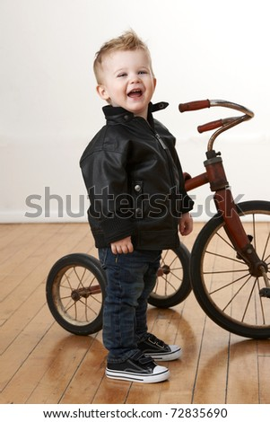 Baby boy in leather jacket standing in front of vintage tricycle.