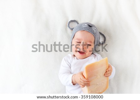 Baby boy in mouse hat lying on blanket with cheese - stock photo