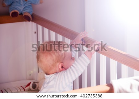Baby boy in waking up in his crib cot in the morning - stock photo