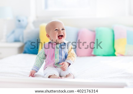 Baby boy in white bedroom. Newborn child in bed with pastel color cushions. Nursery for children. Textile, pillows and bedding for kids. Family morning at home. New born kid tummy time with toy bear. - stock photo
