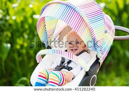 Baby boy in white sweater sitting in white stroller on a walk in a park. Child in colorful rainbow buggy. Little kid in a pushchair. Traveling with young kids. Transportation for family with infant. - stock photo