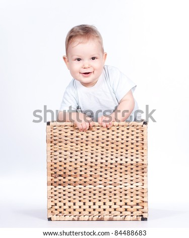 Baby boy in wicker basket on white background