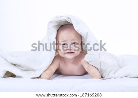 Baby boy is crying under blanket on white background - stock photo