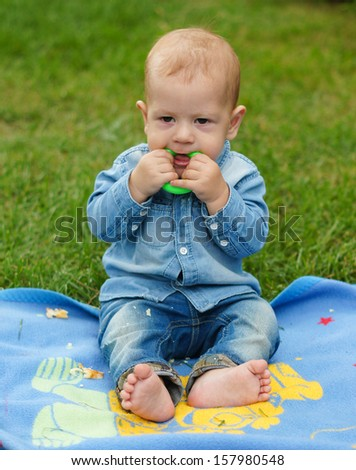 Baby boy is playing on the green grass - stock photo