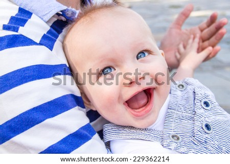 baby boy is smiling broadly while holding his father's hand in a park in summer time - stock photo