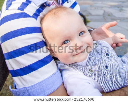 baby boy is smiling while holding his father's hand in a park in summer time - stock photo