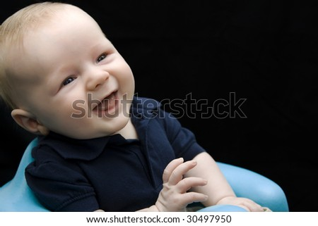 Baby boy laughing wearing polo shirt on black background - stock photo