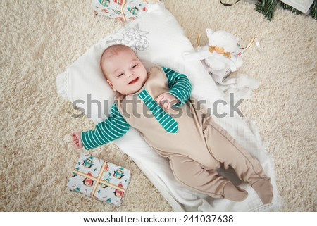 Baby boy laying near gifts - stock photo