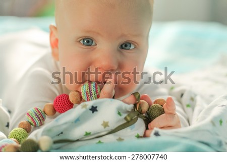 Baby boy laying on the bed, holding knitted necklace, closeup - stock photo