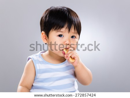 Baby boy learn to eat the finger food - stock photo