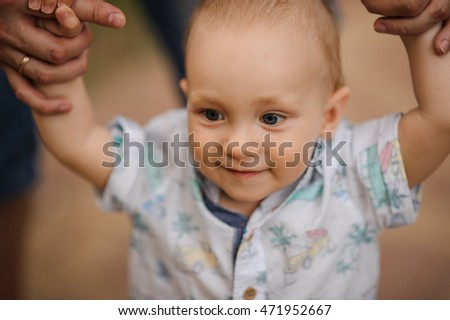Baby boy learning to walk and making his first steps holding hands of father.