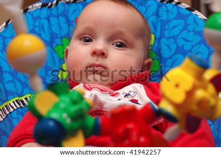 Baby boy looking at multicolor hanging rattles