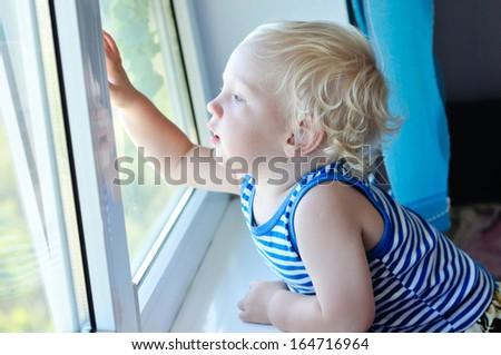 baby boy looking through the window - stock photo